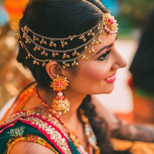 New mathapatti designs   Bridal jewellery trends   Pretty Gota mathapatti with a pink centre   shot by - Dot Dusk photography   Indian bride wearing pretty pink and gold gota earrings for her mehndi