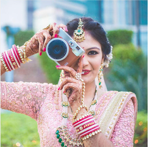Bride taking a photo on a camera | Pink bridal outfit