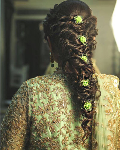 Teej party ideas | Teej Celebrations | Indian bride with a soft braid twist with green small flowers in it | by jasmine beauty care