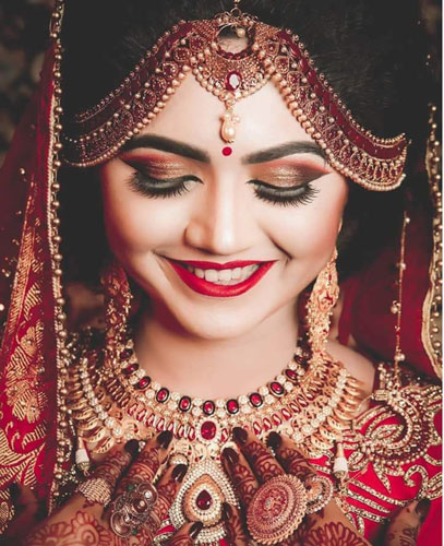 red coloured mathapatti   stunning indian bride   happy bride wearing traditional red an gold bridal jewellery