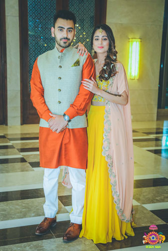 Indian bridal Photos | Delhi Wedding | Kiah and Ron | Indian bride matchingteh groom in her mehndi. | bride in a peach cape and yellow lehengas and groom in in orange kurta with a mustard pocket square and grey waistcoat