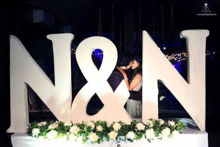 Nindiya and Nirmal | Indian bridal lehenga | Real flower lehenga | The beuatiful couple having a great time together amidst the backdrop pf their cute monogram.