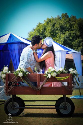 Nindiya and Nirmal | Indian bridal lehenga | Real flower lehenga | The couple sharing a cute moment sitting on a flower studded cart.