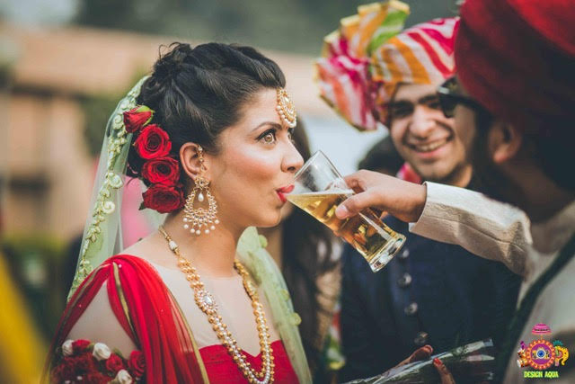 Chitrakshi and Neil | Offbeat wedding in Delhi | Day wedding full of ideas | Indian bride wearing an ivory lehenga with a floral sleeve blouse and a red and pista pastel double dupatta | Indian bride with a red sweetheart blouse with red white and green 3d flower decoupage on the sleeves | Indian bride and groom drinking beer together | photo by Design Aqua | WIttyVows