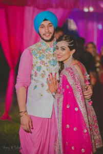 Bavleen and Kushal   Destination wedding in Goa   The bride in a pink outfit sharinga cute moment with her brother in a color coordinated pink and blue outfit.