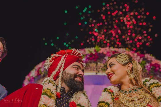 Bavleen and Kushal   Destination wedding in Goa   The bride and groom smile at each other while the rose petals burst in the sky.