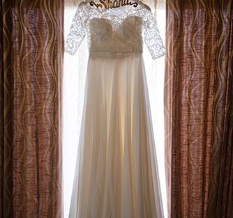 Joshua and Shona   Christian wedding   DIY ideas   The bridal white gown hnaging on the customised hanger looks great.