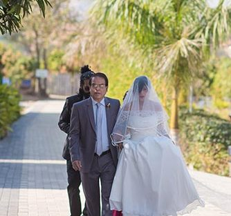 Joshua and Shona   Christian wedding   DIY ideas   The bride walking down the aisle with her father.