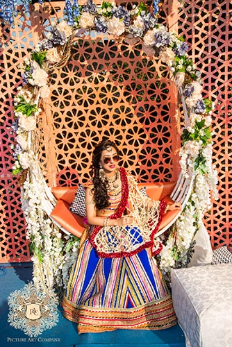 Nayana and Jai | Amazing Delhi wedding | Proposal story | Proposal ideas | The bride in a multicolored outfit sitting and posing with her shades on.