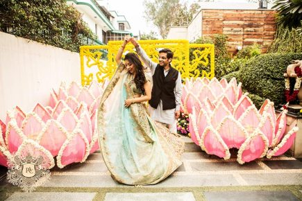 Nayana and Jai | Amazing Delhi wedding | Proposal story | Proposal ideas | The bride and groom dancing together amidst the lotus flower decor.