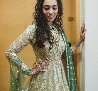 Jaya and Anish | Roka ceremony | Flower decor | The bride in a beige gown and green dupatta posing in her kundan jewelry.