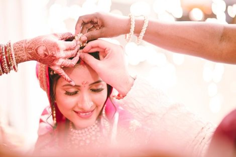 Sagar and Subiya | Destination wedding in Bali | The bride smiling while being applied sindoor.