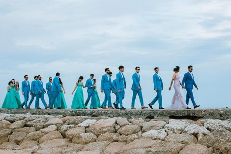 The bride and the groom walking with their perfectly coordinated gang of friends.
