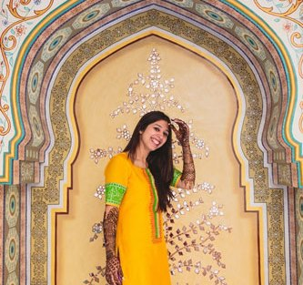 Nimisha and Hemant   Temple wedding in Delhi   The bride posing in a yellow outfit with her mehendi.
