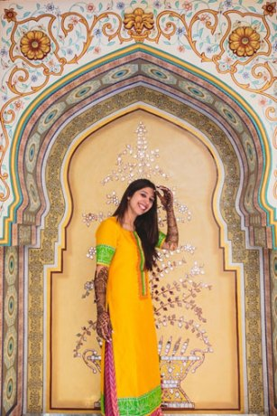 Nimisha and Hemant | Temple wedding in Delhi | The bride posing in a yellow outfit with her mehendi.