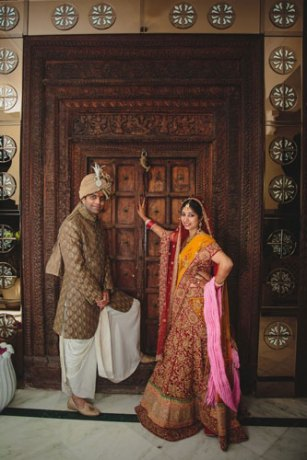 Nimisha and Hemant | Temple wedding in Delhi | The bride and the groom giving a royal pose in front of the vintage wooden door.