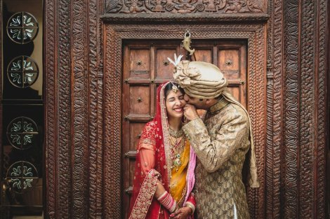Nimisha and Hemant   Temple wedding in Delhi   The groom whispering to the bride while posing in front of a vintage door.