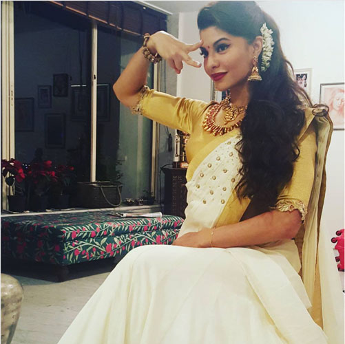 Bridesmaid's Dress ideas bollywood flaunted a.k.a Totally trending Wedding Outfit ideas for the Bride's Best friend | Jacqueline Fernandes in a pretty ivory and gold saree with a gold yellow quarter sleeves blouse and South Indian gold jewellery paired with a traditional gajra