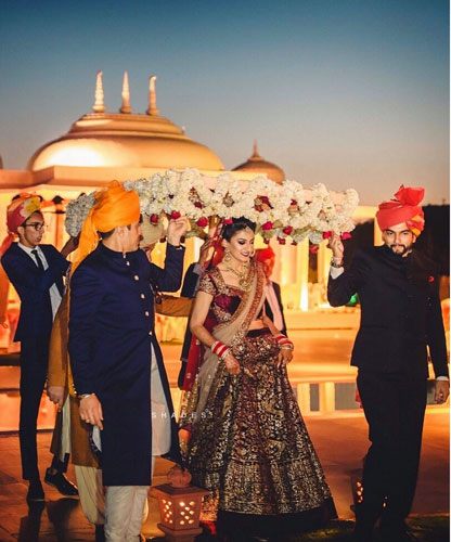 new phoolon ki chadar ideas for a perfect bridal entry | bride in a deep red lehenga walking under a beautiful phoolon ki chadar in white flowers