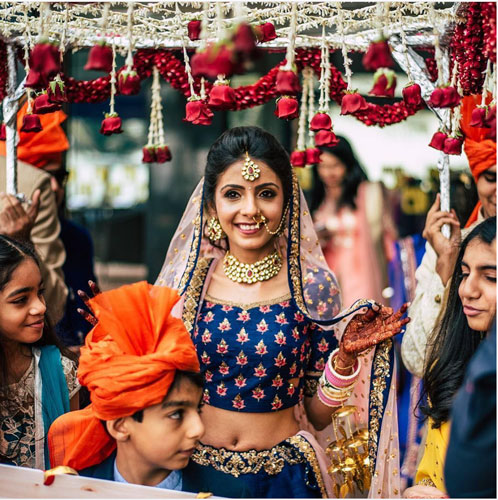 new phoolon ki chadar ideas for a perfect bridal entry   bride in a blue lehenga walking under a white phoolon ki chadar lehenga with rose tassels