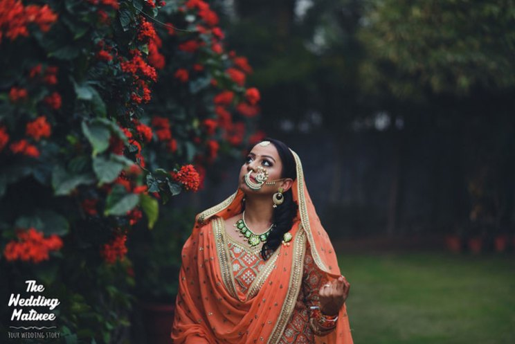 Dupatta draping style with ghoomghat and cross body wraparound | Indian bride in a pretty orange and gold lehenga with a gorgeous gold Nath | wedding matinee