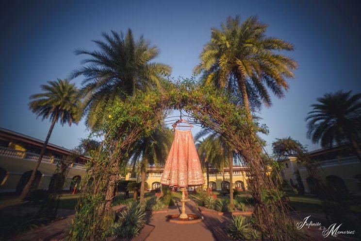 Siddharth and Rutika | Super cute Goa wedding full of beach wedding ideas | photo by Infinite Memories  | pretty orange hanging lehenga at a beach on palm trees