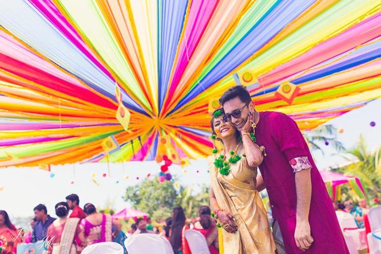 Siddharth and Rutika   Super cute Goa wedding full of beach wedding ideas   photo by Infinite Memories    colourful haldi and mehendi with colourful fabric canopy and kites hanging as decor