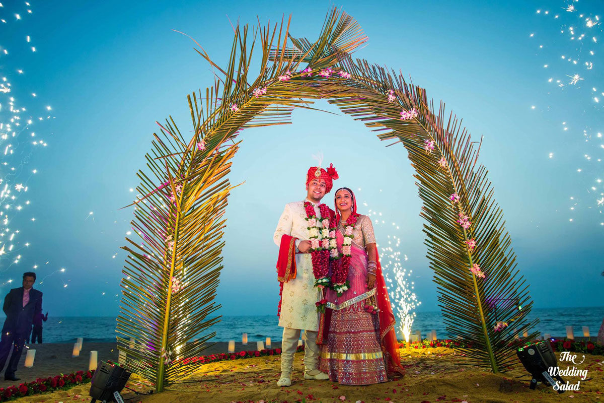 guide to planning a beach wedding in india | Goa wedding with bride and groom standing under a plan leaf gate with sparklers