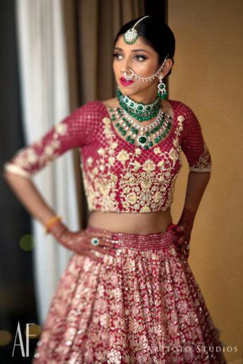 Indian bride in a beautiful red bridal lehengas with Kundan and emerald wedding jewellery