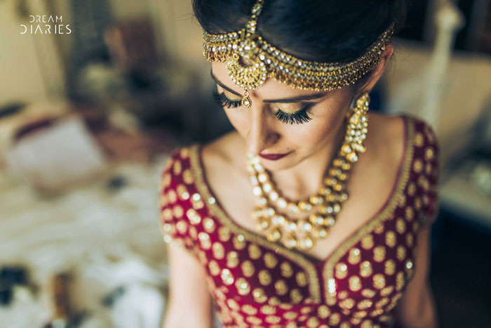 Indian bride wearing a red and gold bridal lehengas blouse with gold wedding jewellery