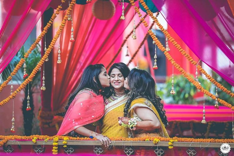 indian bride and her sister kissing their mother under colourful drapes for Mehndi decor and gorgeous latkans and paper lanterns was Mehndi decor