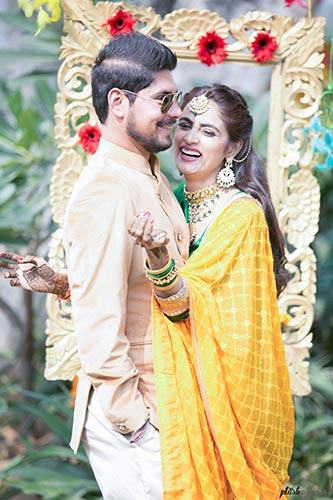 aditi and Rohan | Delhi weddng for a model bride | Couple posing at mehendi in front of a frame | plush affairs photography