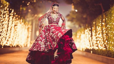 Indian bride happily prancing in her maroon lehengas by Manish Malhotra
