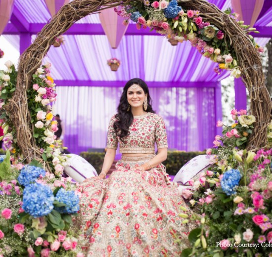 Pastel bride in purple and green mehendi setting with foliage swing