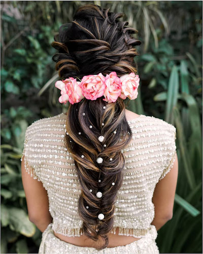 stunning fishtail braid with curled braid with beads and a floral carnation midsection Diwali party hairstyles
