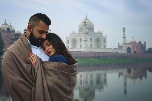 couple snuggling in a blanket in front of the Taj Mahal | pre wedding shoot for indian couples | Ericka Virk