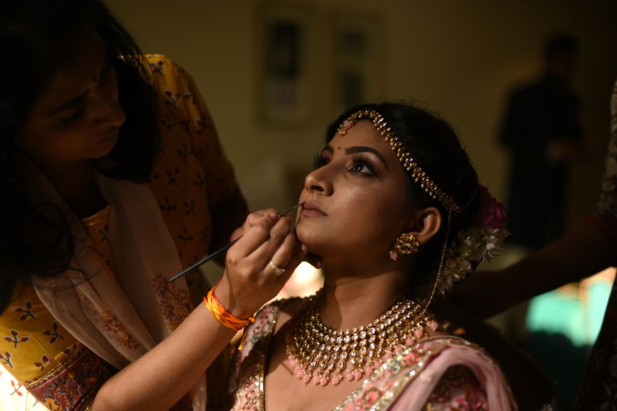 indian bride while getting ready | Bridal Lehenga Designed by the Bride