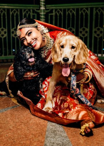 bride posing with her pet dogs  eco friendly wedding