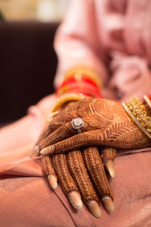 indian brides hands adorned with henna | engagement ring