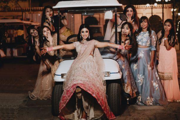 bride posing with bridesmaids | Destination Wedding in Udaipur