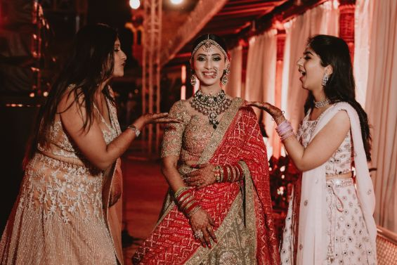 bride posing with her sisters | Destination Wedding in Udaipur