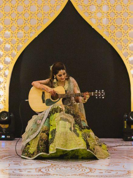 indian bride playing  guitar on sangeet night   Printed Lehenga  & a Gorgeous Off Shoulder Blouse - Megnha & Devansh