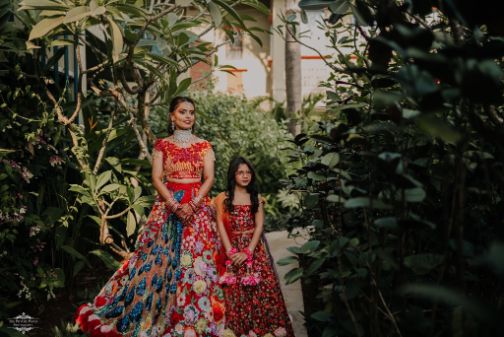 indian bfride posing with her niece | Stunning Colourful Wedding Lehenga