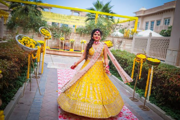 twirling bride in lehenga , yellow lehenga | #wittyvows #indianbrides pool side wedding | indian wedding pool side | destination wedding outside delhi | haldi ceremony | floral decoratioms | indian parents and bride | realwedding | Kitsch mehendi decor