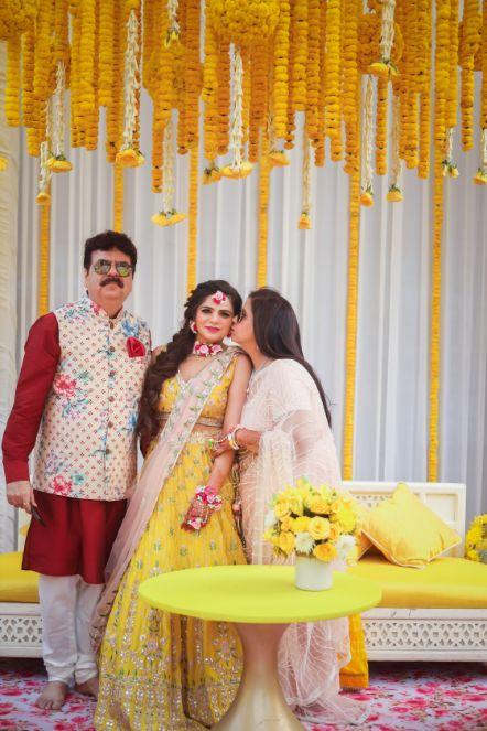 destination wedding outside delhi | haldi ceremony | floral decoratioms | indian parents and bride | realwedding |  Kitsch mehendi decor