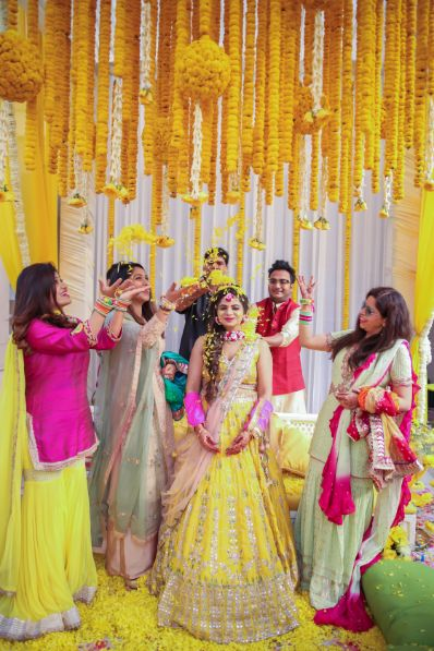 flower shower for indian brides | twirling bride in lehenga , yellow lehenga | #wittyvows #indianbrides pool side wedding | indian wedding pool side | destination wedding outside delhi | haldi ceremony | floral decoratioms | indian parents and bride | realwedding | kitsch mehendi decor