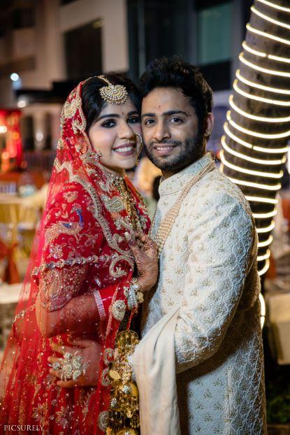 indian couple posing Mumbai wedding manish malhora lehenga | indian bridal red lehenga | indian bridesmaid