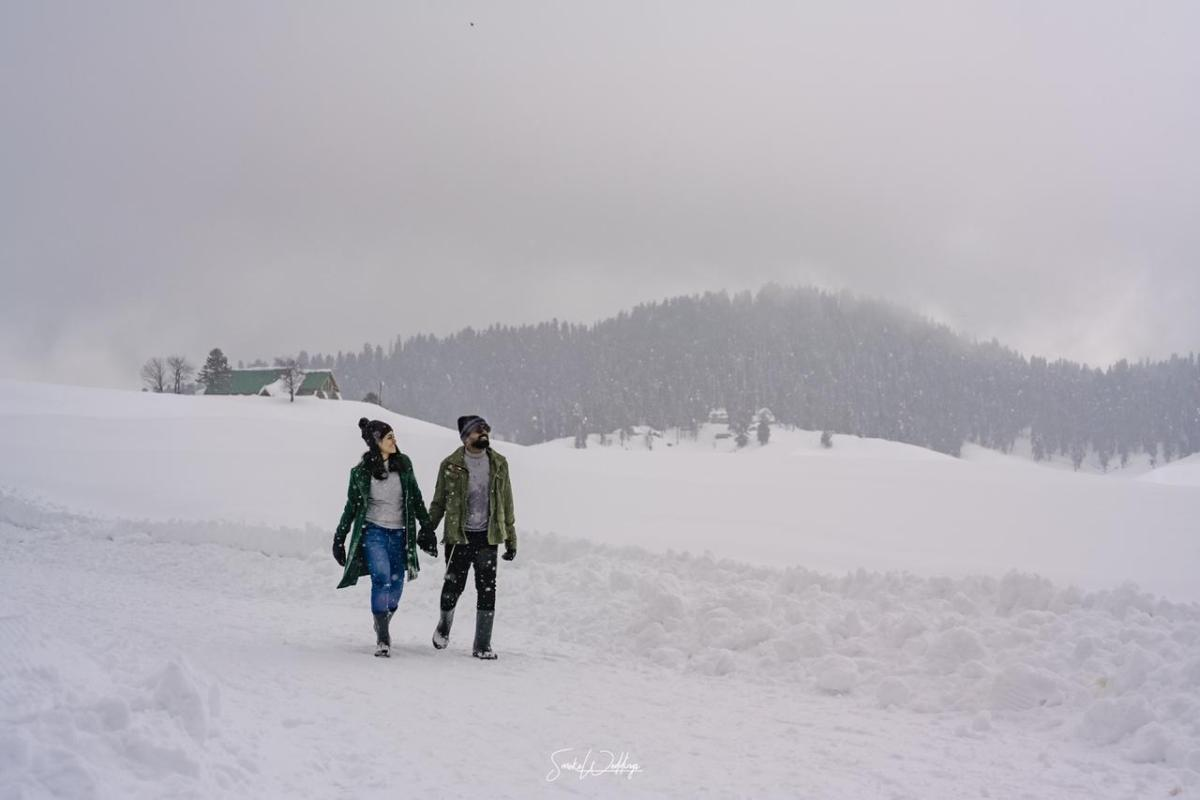 pre wedding shoot ideas , snow , snow fall wedding couple , indian couple in snow , intimate South Indian wedding | peach lehenga | pre wedding shoot