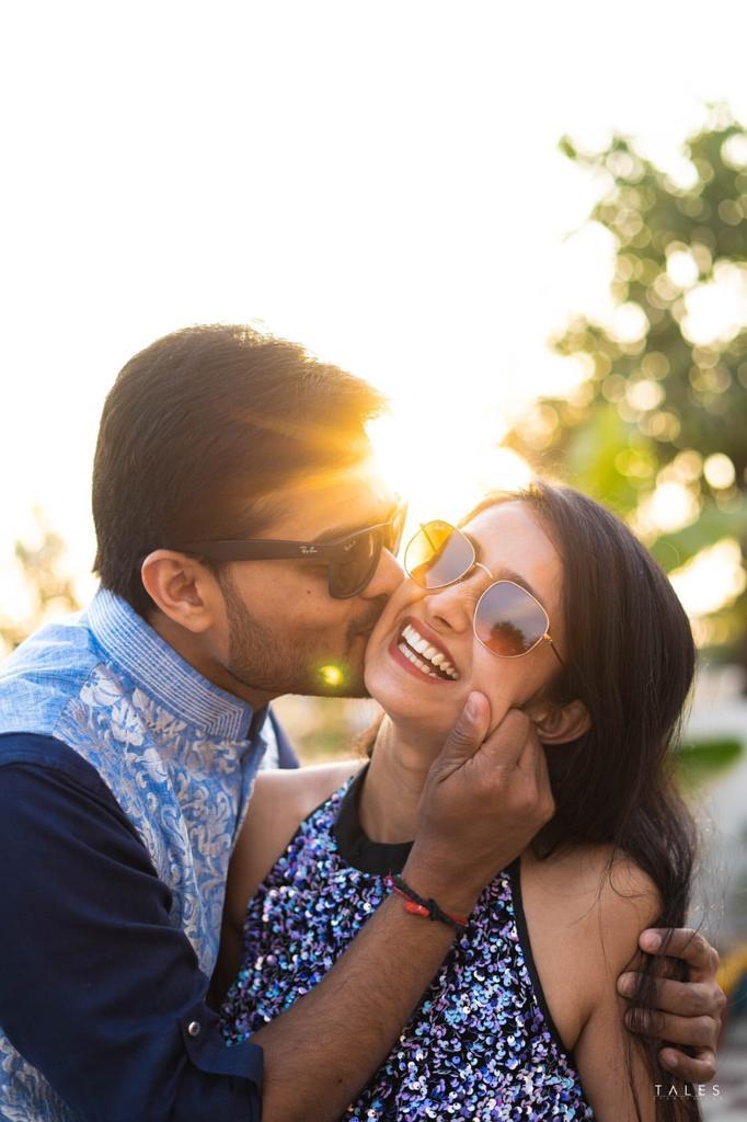 couple kissing , blue , happy , bridal looks , wedding look , red lehenga , bridal mehendi , floral hands , floral jewellery , intimate wedding, personalised wedding ideas