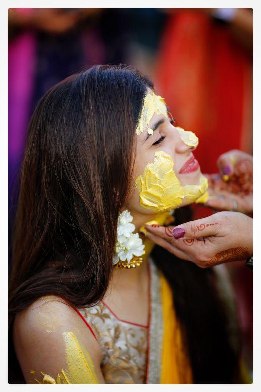 indian bride adorned with haldi for her wedding